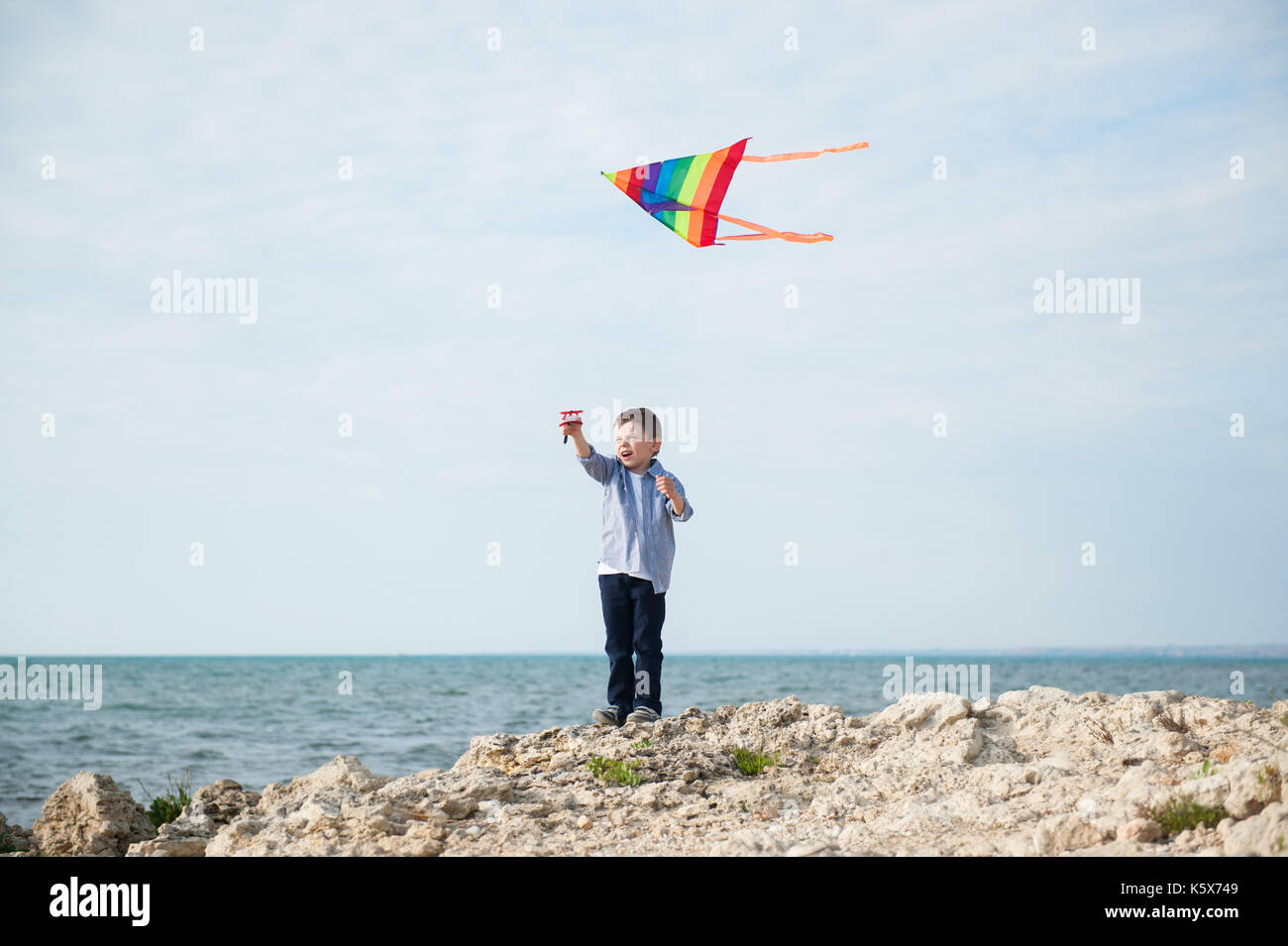 happy small boy holding a kite flying in the sky on the background of sea - Stock Image
