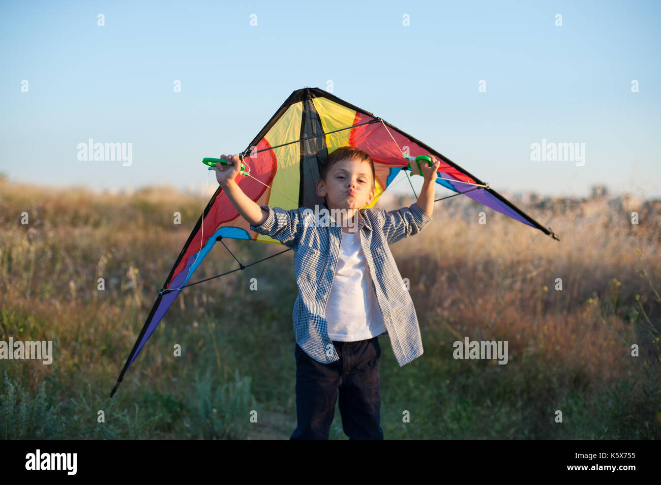 Grimacing funny boy holding a kite behind his shoulders - Stock Image