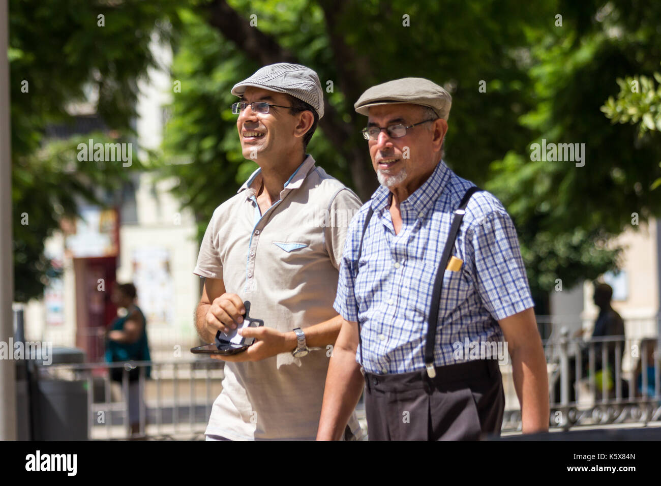 Father snd son walking in Malaga, Spain wearing flat caps - Stock Image