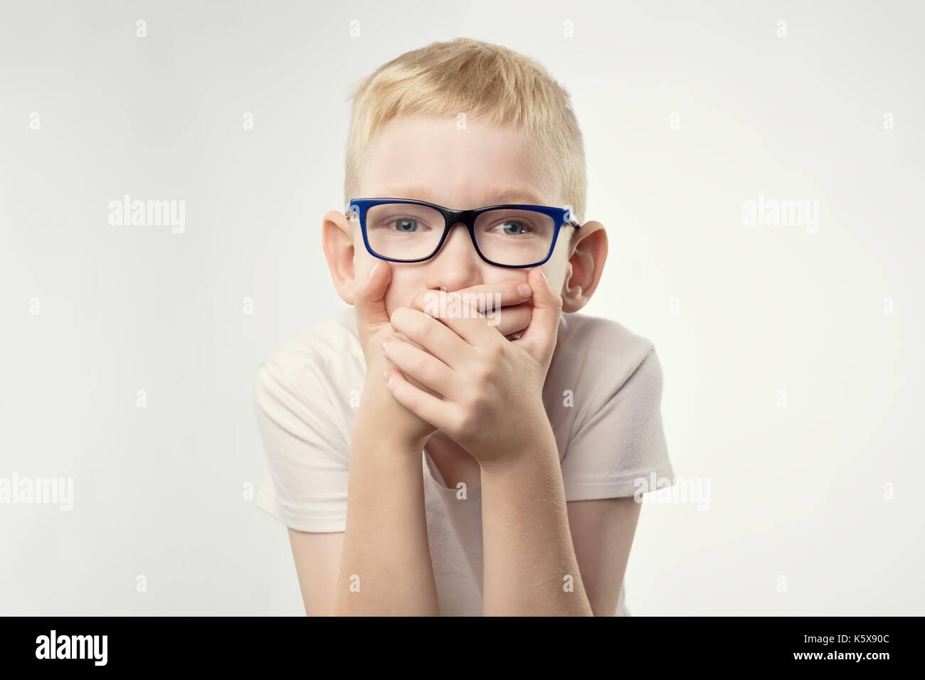 young boy kid shows sign hand gesture holding finger on lips. - Stock Image
