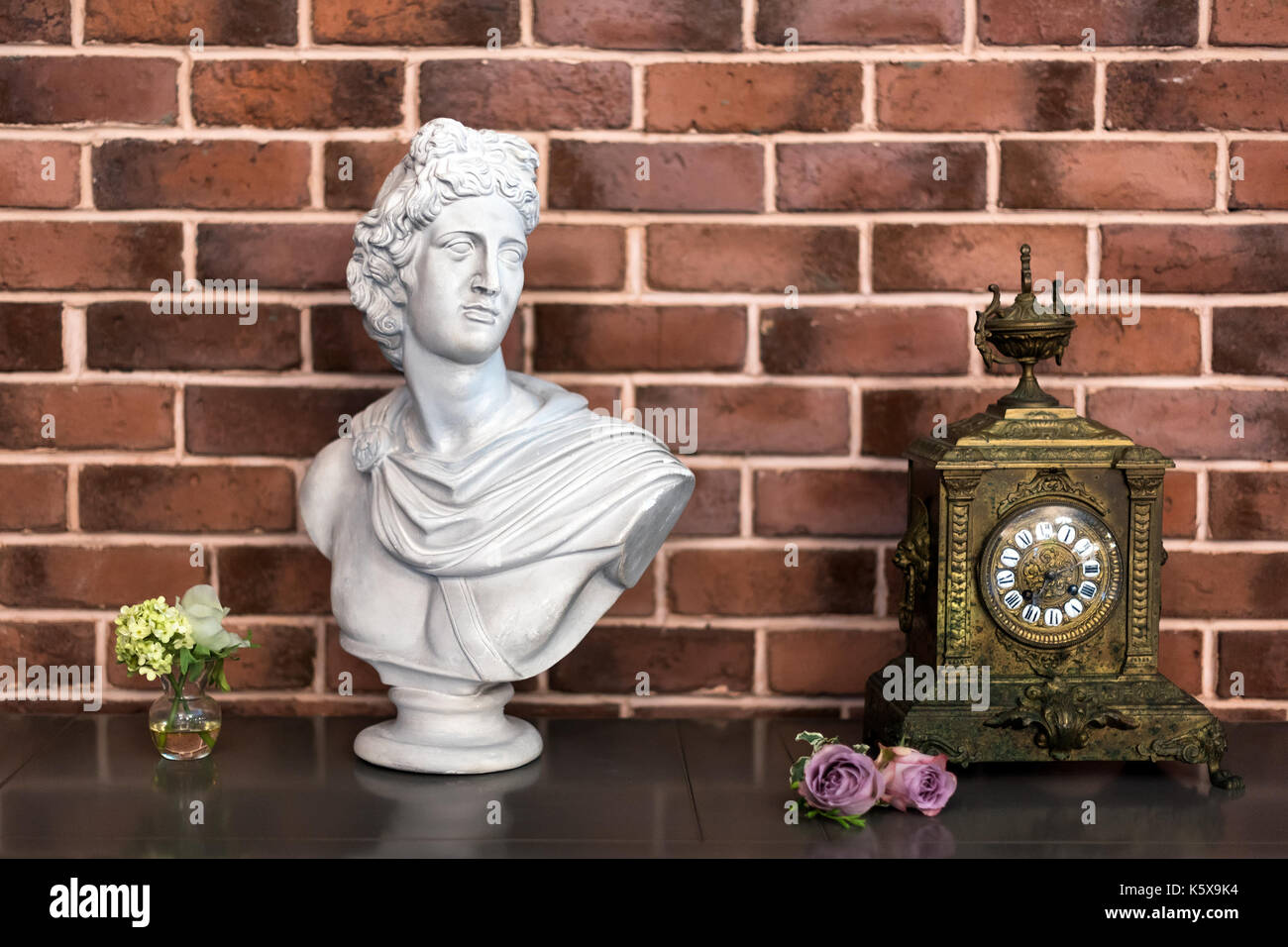 White plaster bust sculpture portrait of a young man and old clock on the table, details of luxury interior in classic style. - Stock Image