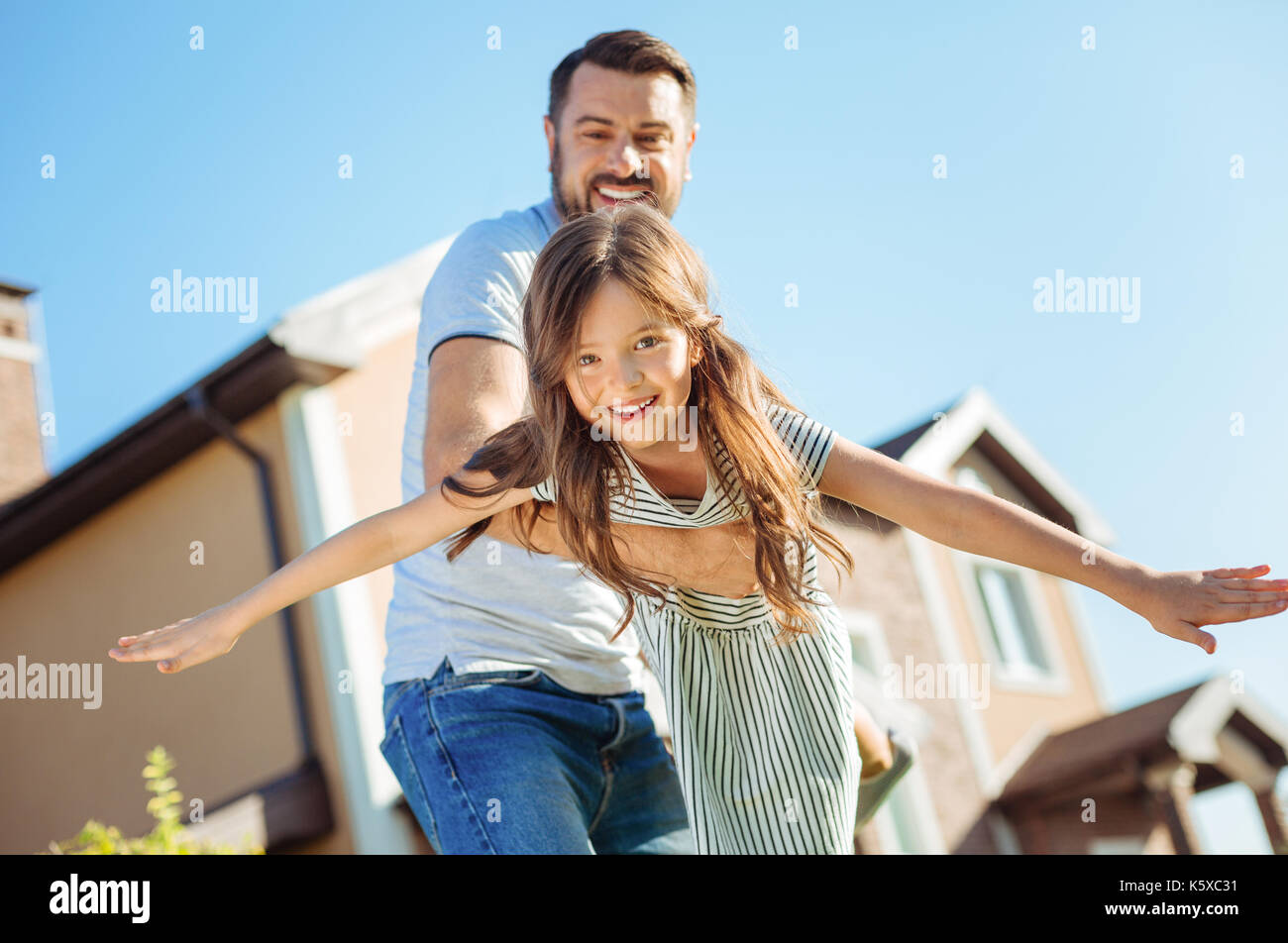 Smiling father playing with his happy daughter - Stock Image