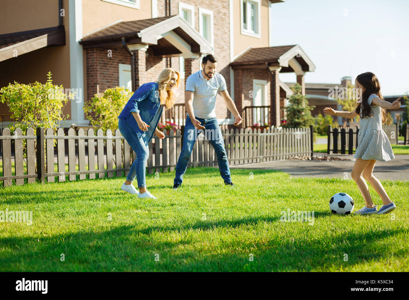 Little girl playing football with her parents - Stock Image