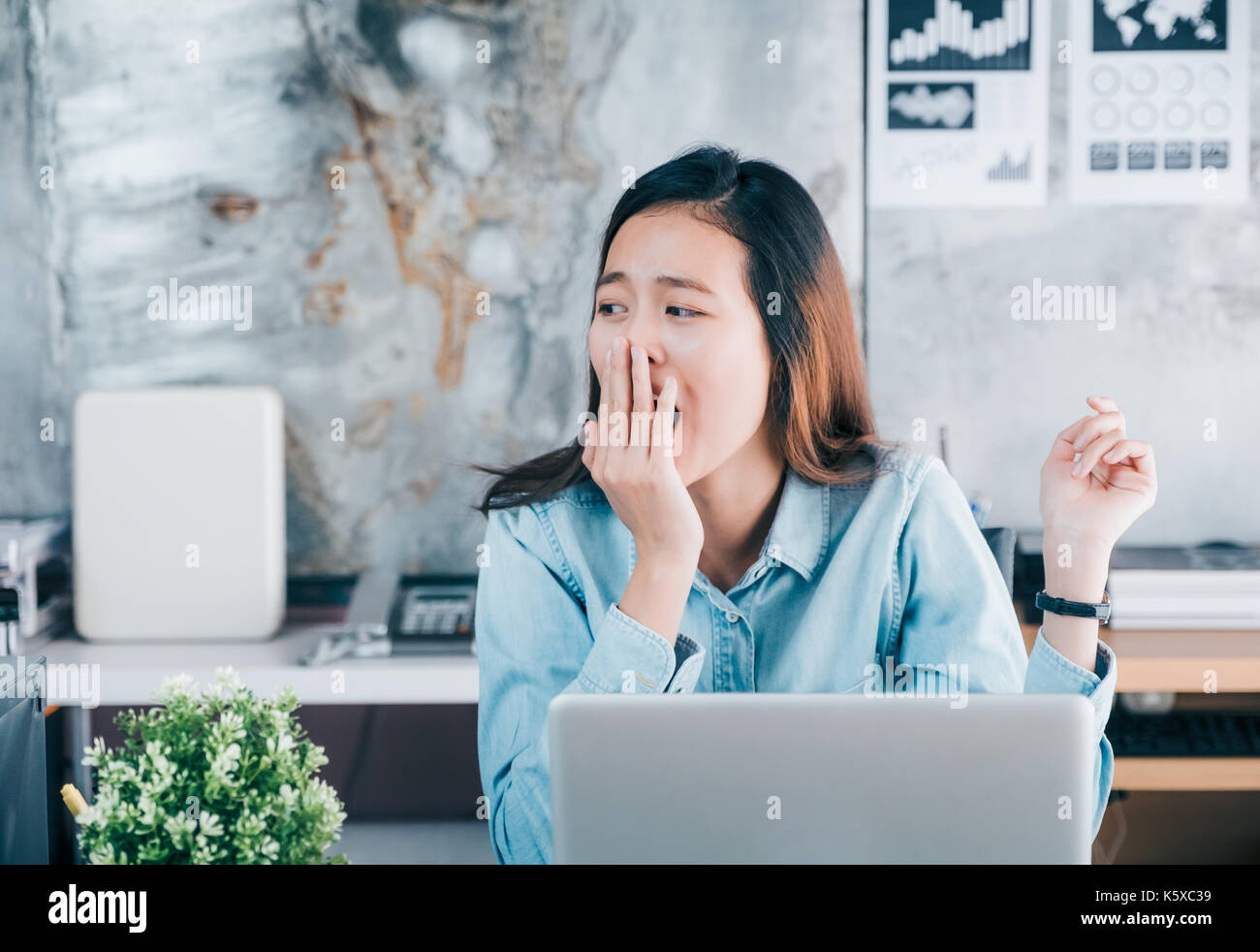 Young asian casual businesswoman yawn in front of laptop computer and looking through office window with bored feeling ,hard work concept - Stock Image