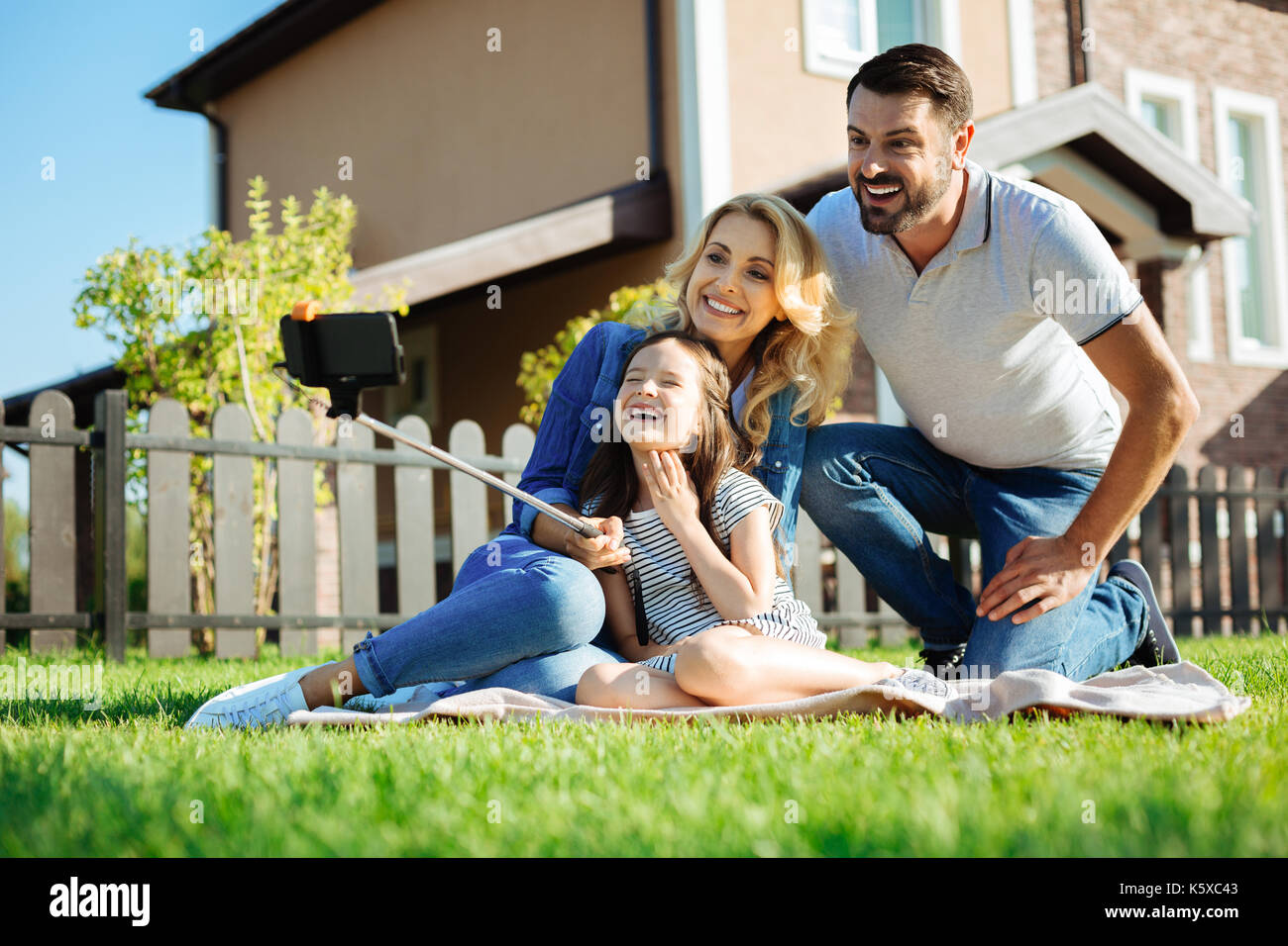 Adorable girl taking selfies of her family on picnic - Stock Image