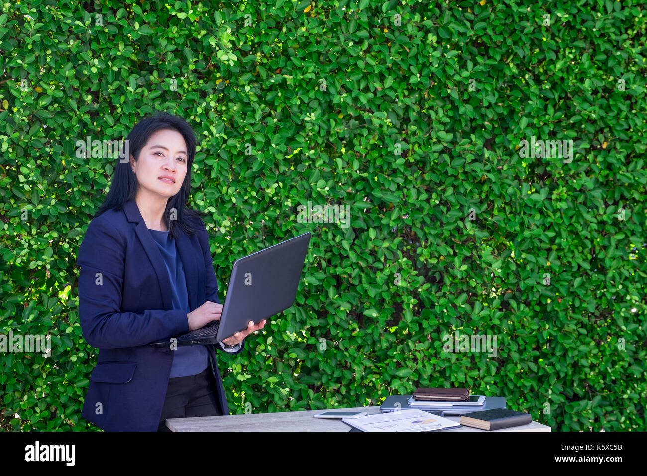 Asian Busineswoman using laptop computer working outside office at green hedge,Moblie office concept. Stock Photo