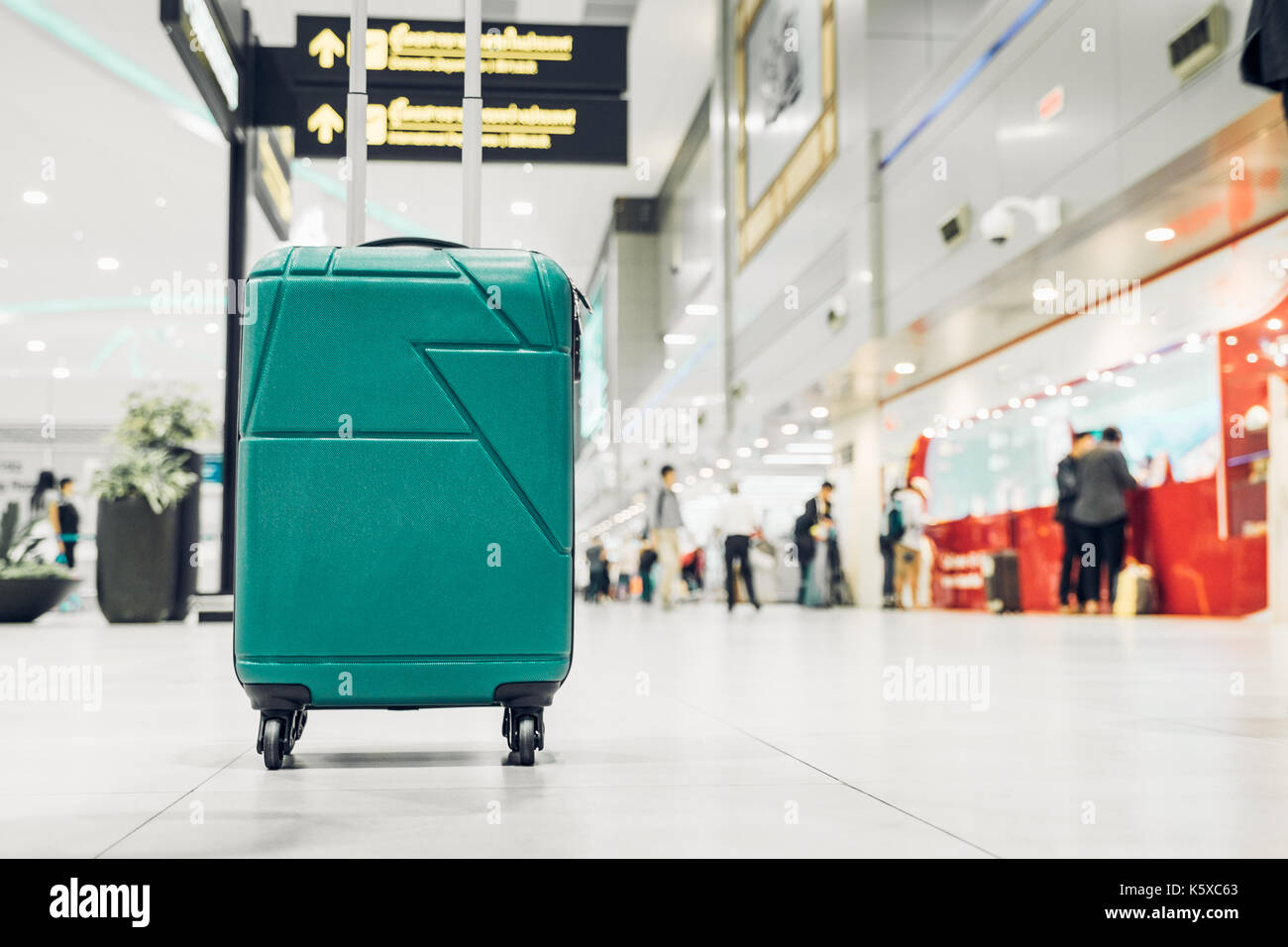 Suitcases in airport departure terminal with traveler people walking in background,Holiday vacation concept, Business trip,selective focus on suitcase - Stock Image