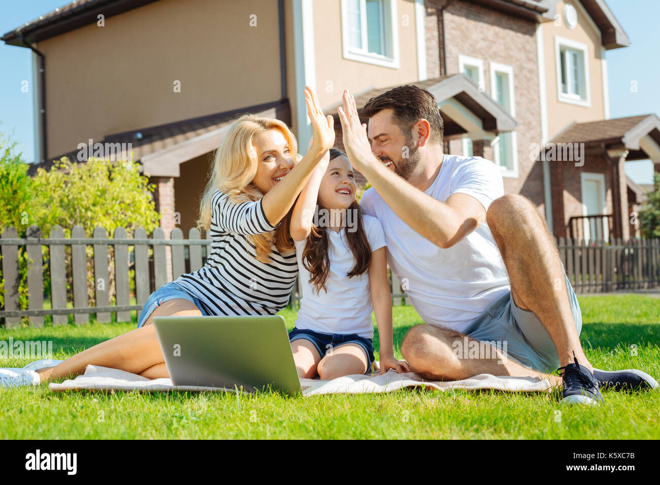Cheerful young family high-fiving each other on picnic - Stock Image