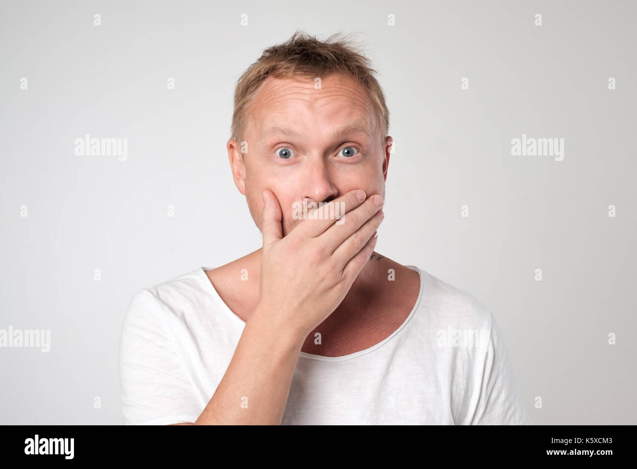 young caucasian man shows sign hand gesture holding finger on lips. - Stock Image