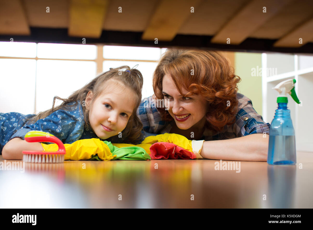 Mother and daughter do the cleaning in the house. Happy woman and little child girl wiped the floor. Stock Photo