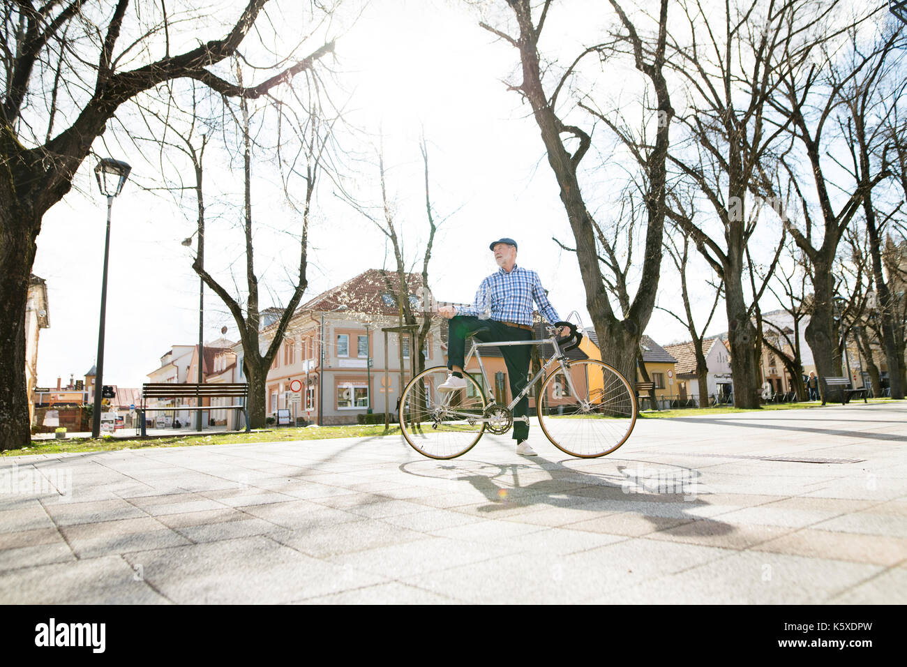 Senior man in blue checked shirt with bicycle in town. - Stock Image