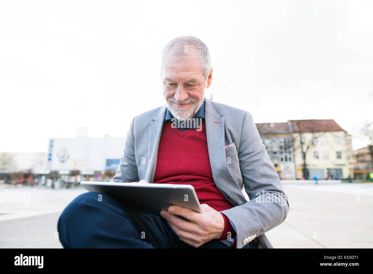 Senior man in town sitting on bench, working on tablet - Stock Image