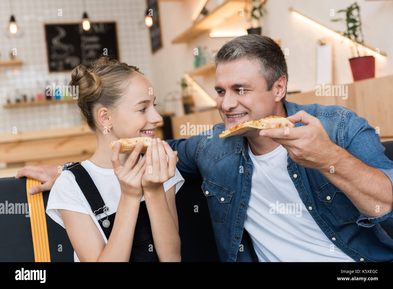 father and daughter eating pizza - Stock Image