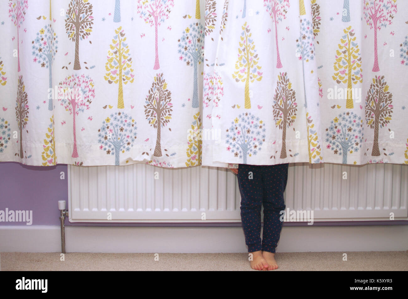 Child hiding behind curtains - Stock Image