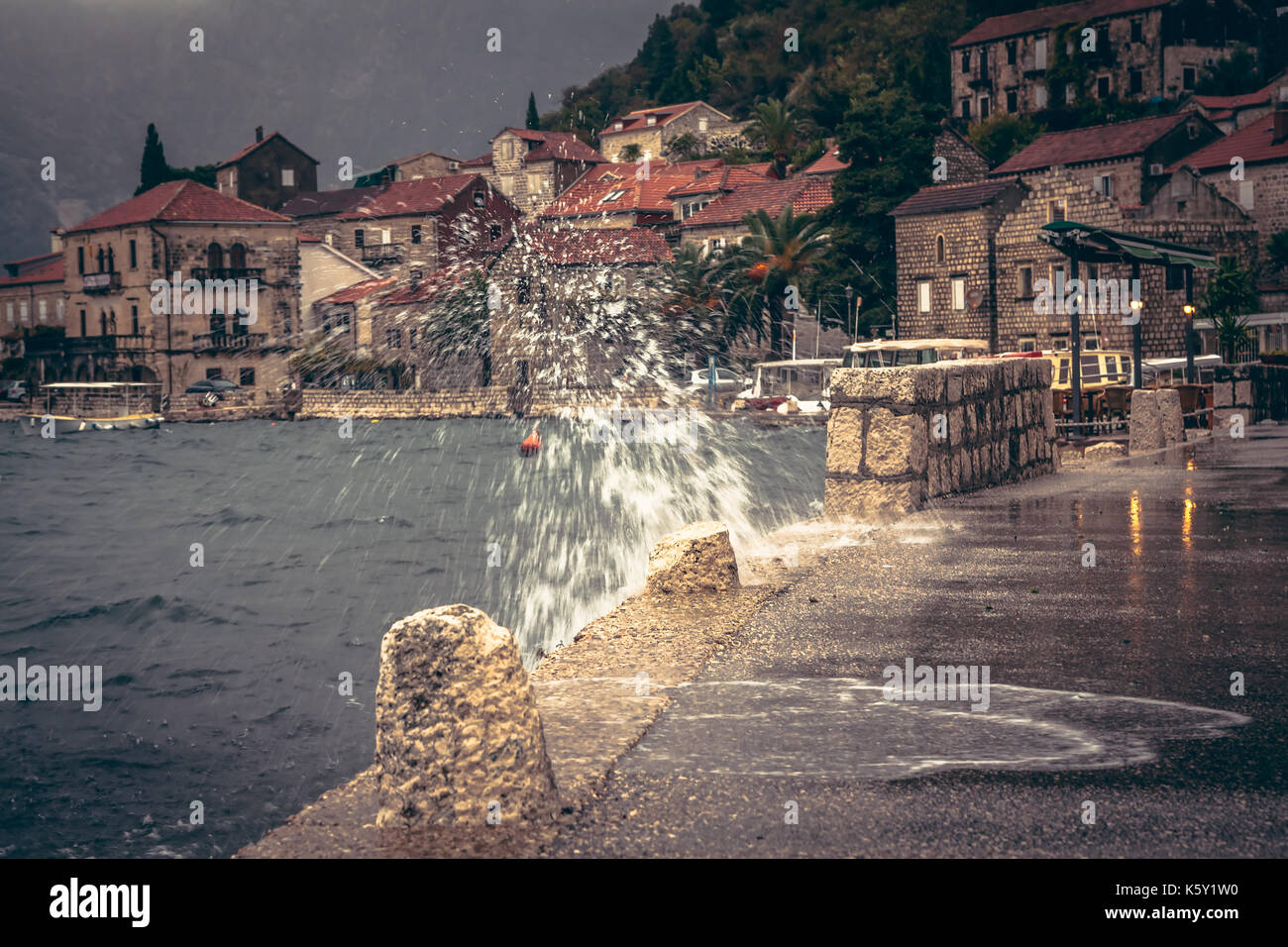Promenade in rainy overcast day with puddles and splashes in old European city Perast on blurred city background - Stock Image