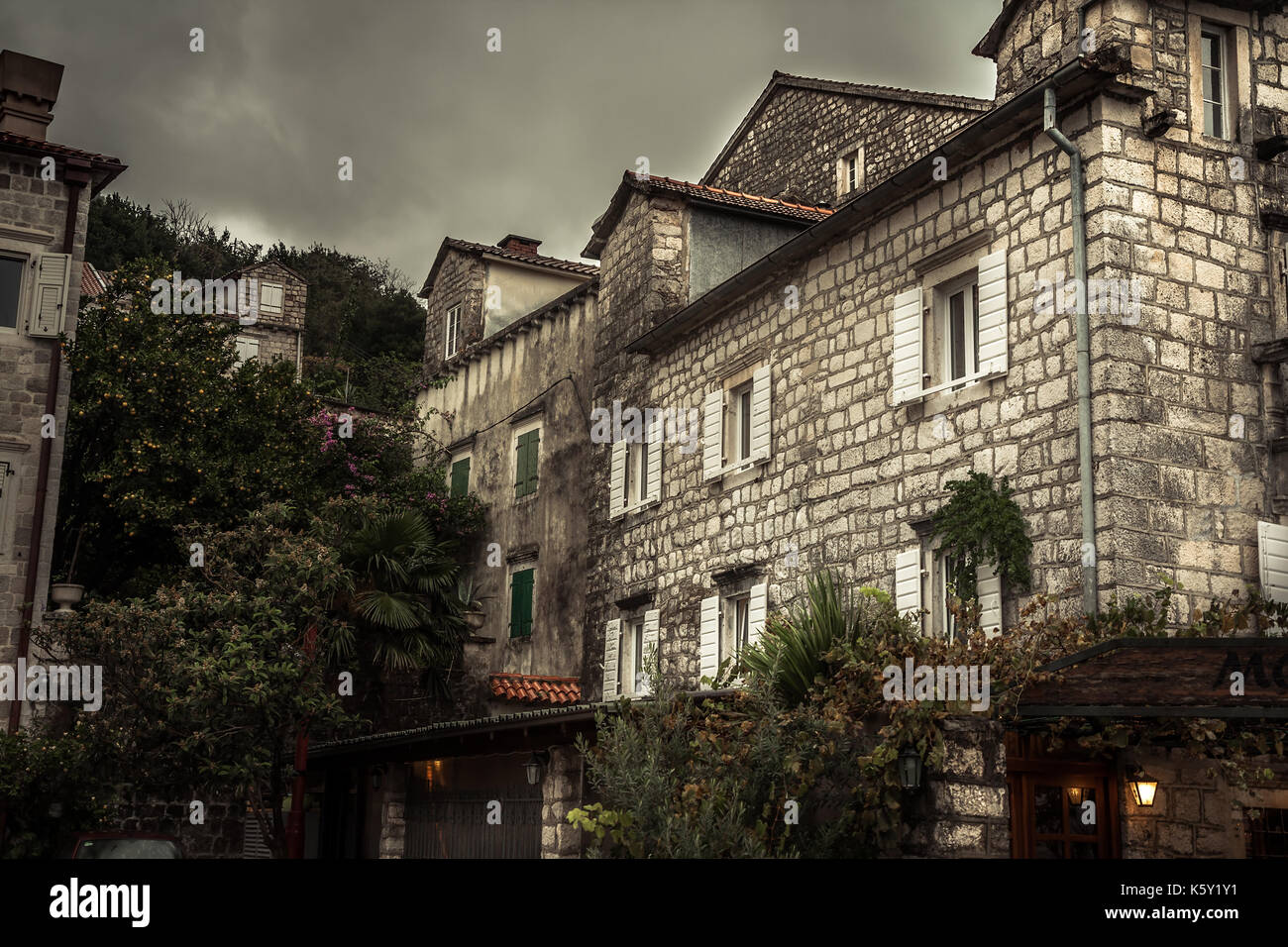 Vintage medieval city street with stone building exterior in overcast day during raining autumn season in old European city Perast with medieval archi - Stock Image