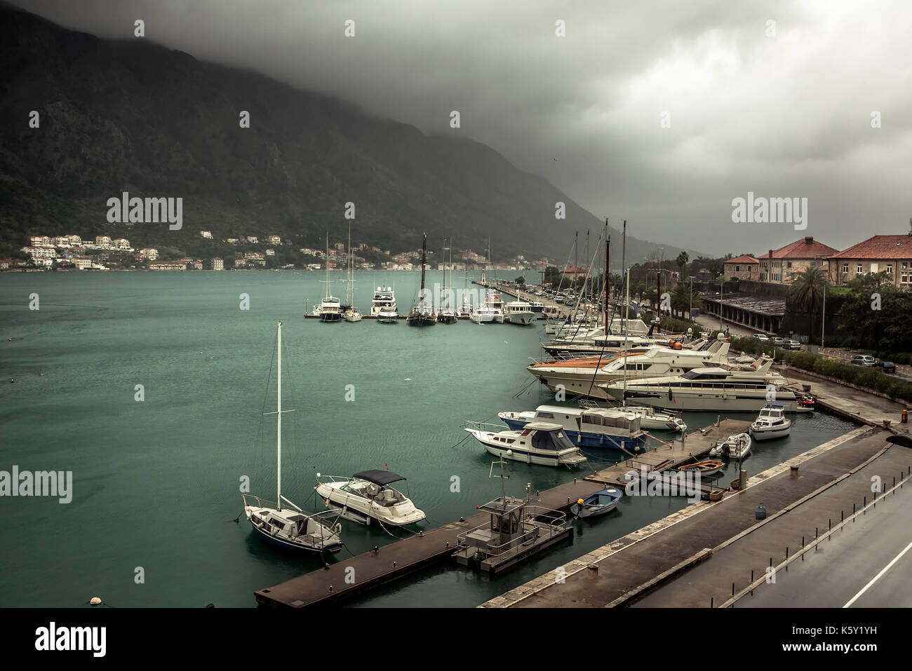 Marine sea port with moored  luxury yachts and boats in medieval Kotor bay in Montenegro in overcast rainy autumn day - Stock Image