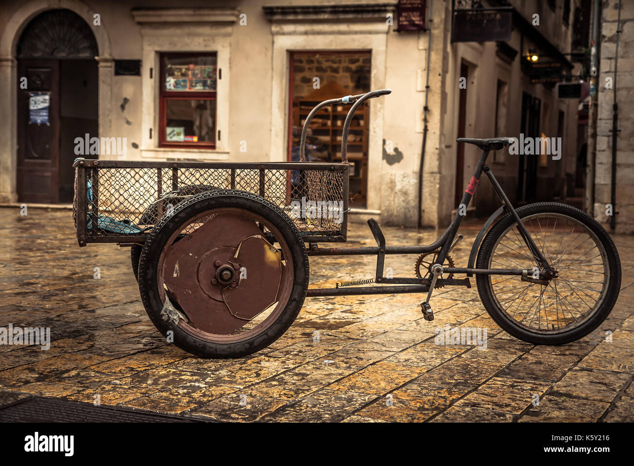 Retro bicycle on vintage europe medieval plaza with stone pavers in overcast day during raining autumn season in old European city Kotor with medieval - Stock Image