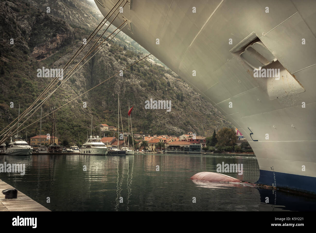 Marine sea port with moored cruise nautical vessel in medieval Kotor bay in Montenegro in overcast rainy autumn day - Stock Image