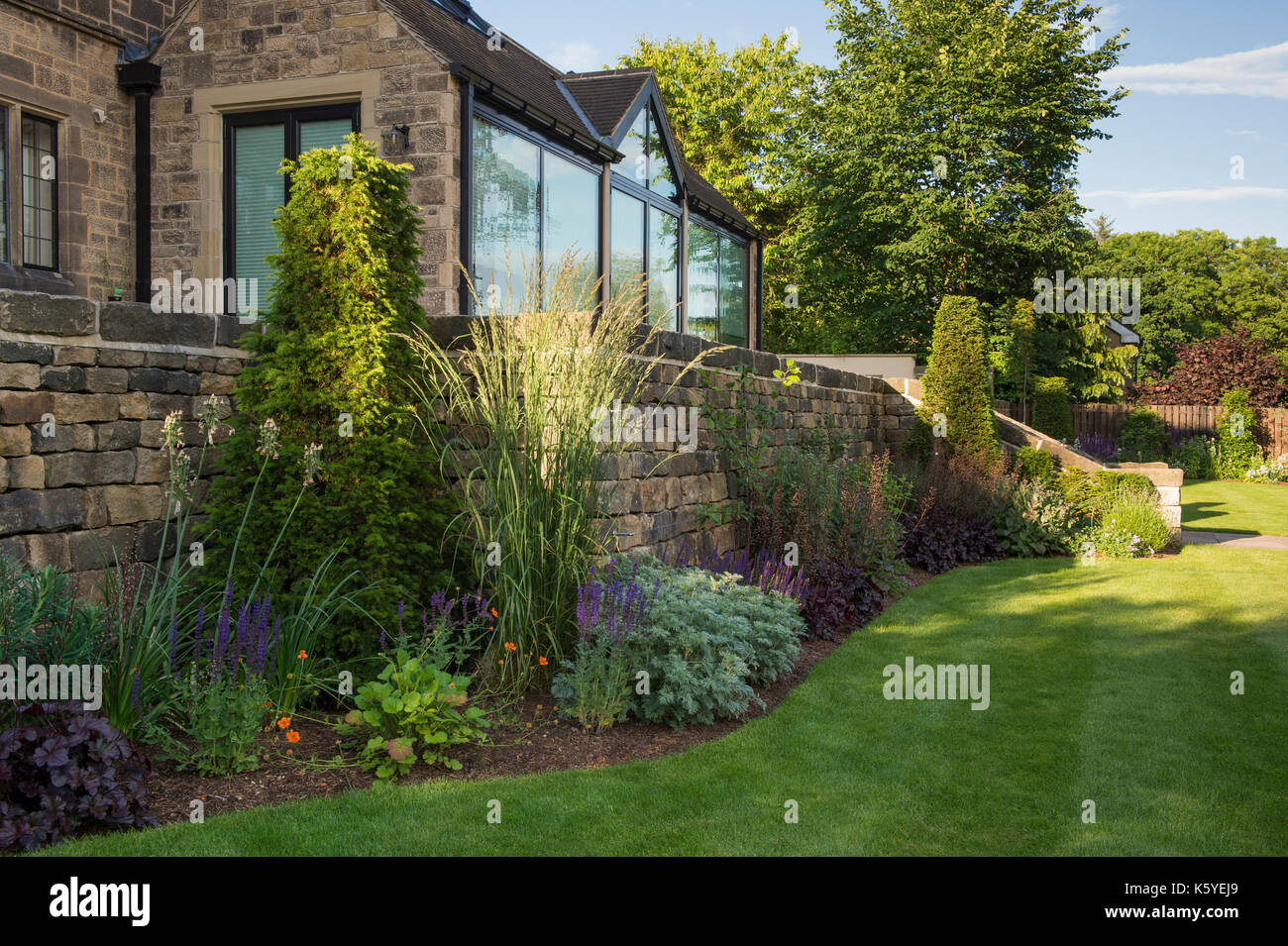 Beautiful, private, traditional, landscaped, country garden, West Yorkshire, England, UK - summer flowering plants on herbaceous border by house. - Stock Image