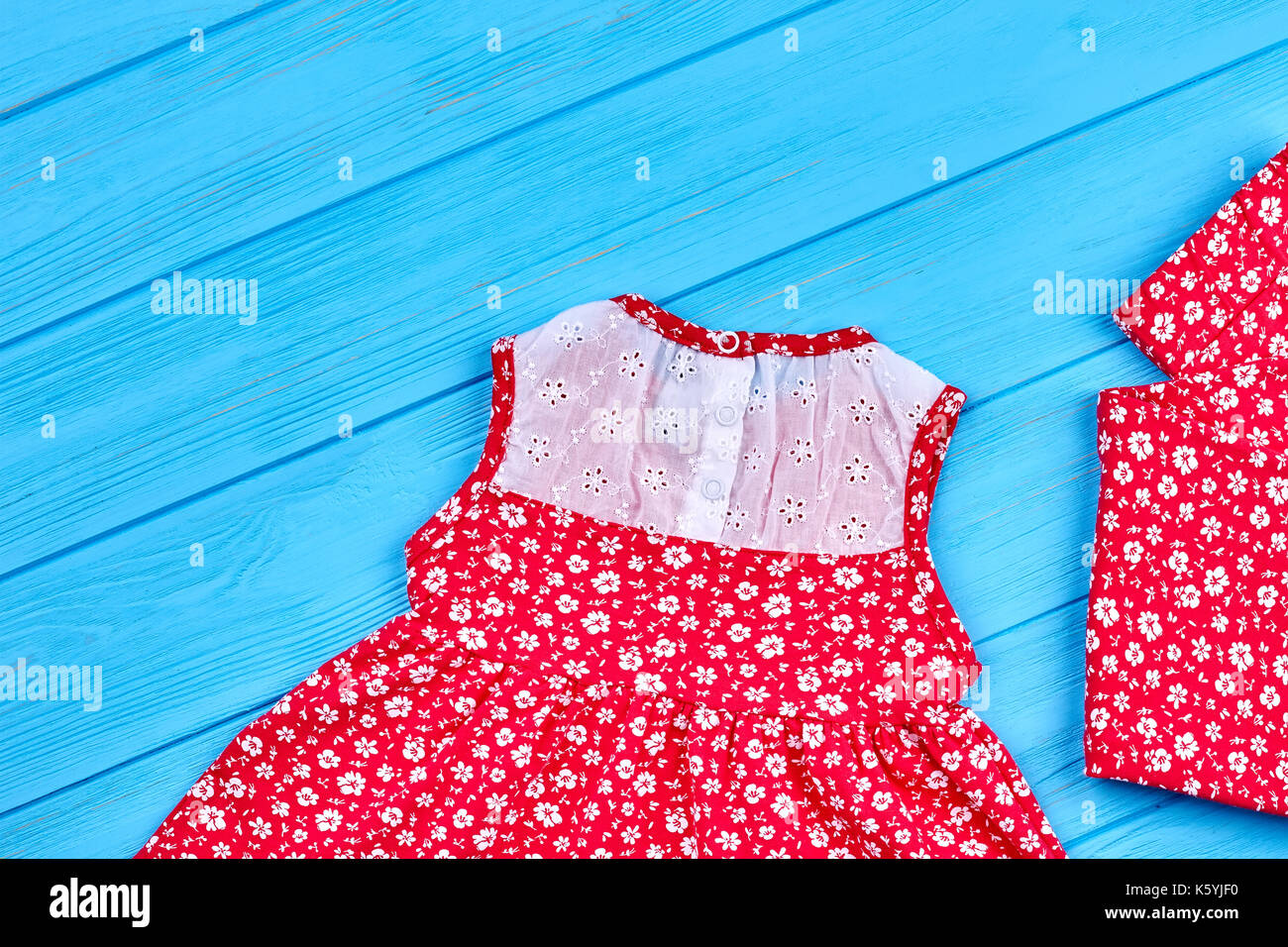 ef3096a76719 Set of baby-girl summer apparel. Beautiful red blouse and pants in small  floral print for little girls, blue wooden background.