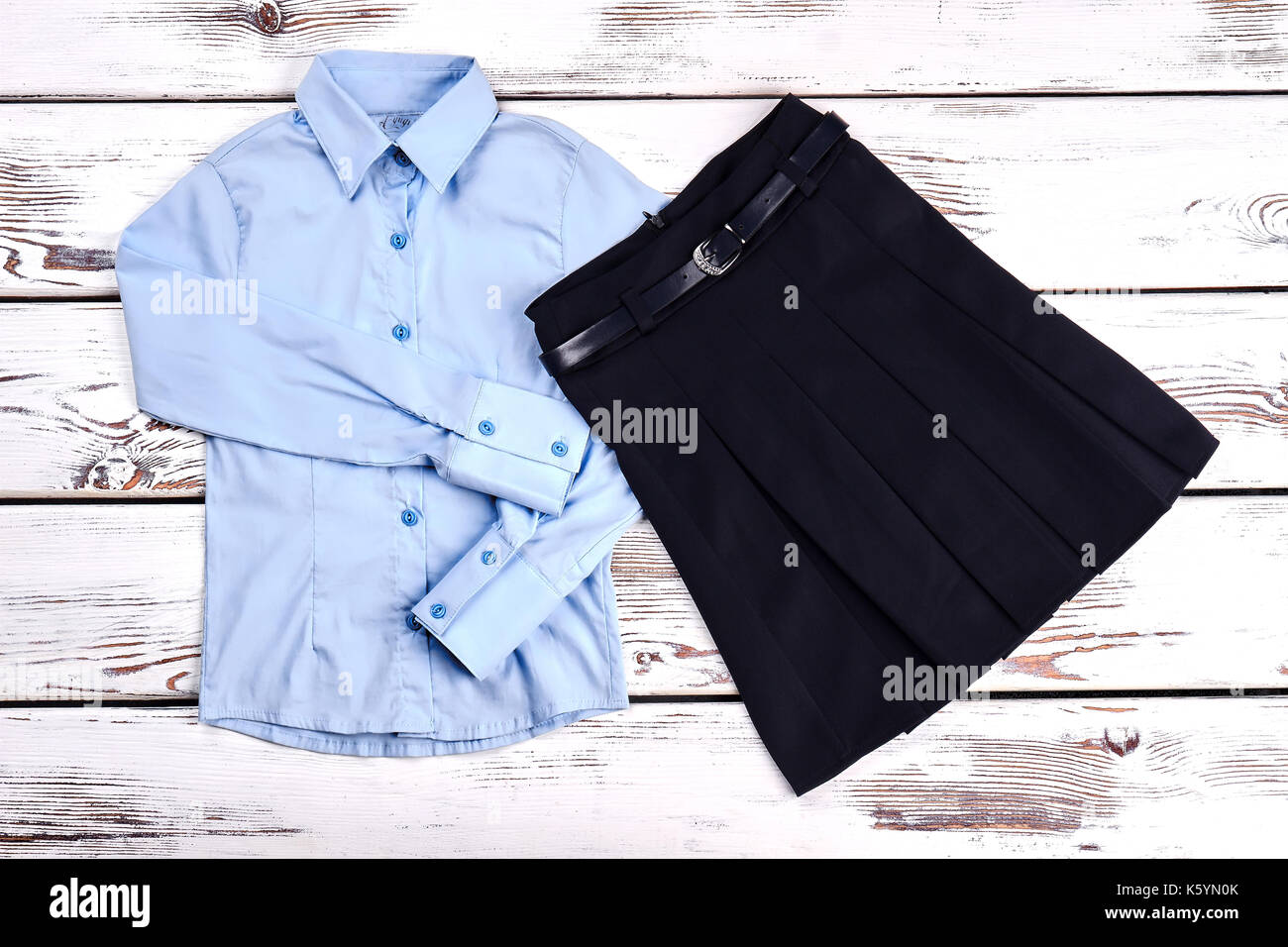 8cc9fd38e8 New collection of girls school uniform. Light blue blouse and black pleated  skirt for girls, top view. Girls school fashion outfit.