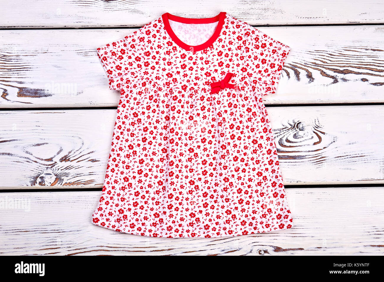 088883ecd71 Toddler girl cute printed top. Baby-girl vintage print summer dress on  white wooden background. Kids organic clothes.