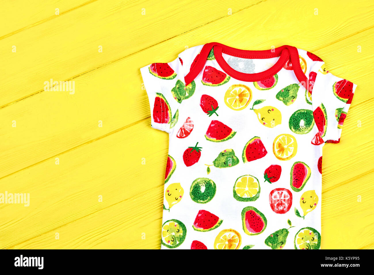 f5f3677ed22 Newborn child beautiful summer romper. Baby short sleeve bodysuit on yellow  wooden background. Hot sale infants summer garment.