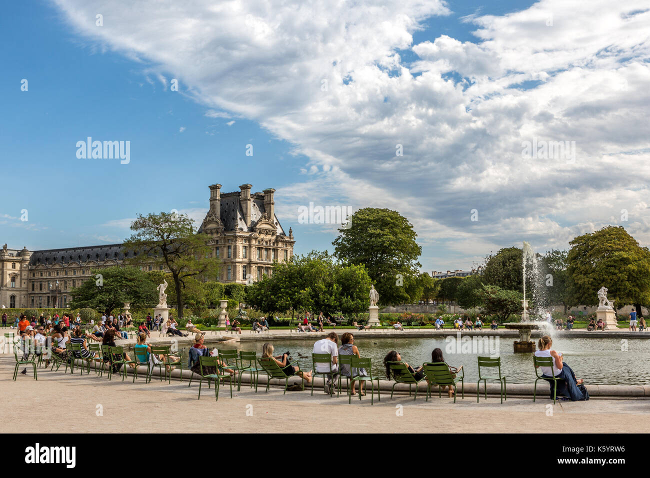 People sitting around the octagonal basin along the Tuileries Garden in Paris - Stock Image