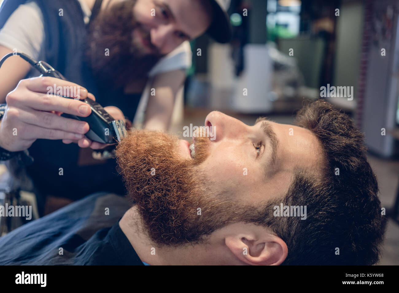 Close-up of the head of a man and the hand of a barber trimming  - Stock Image
