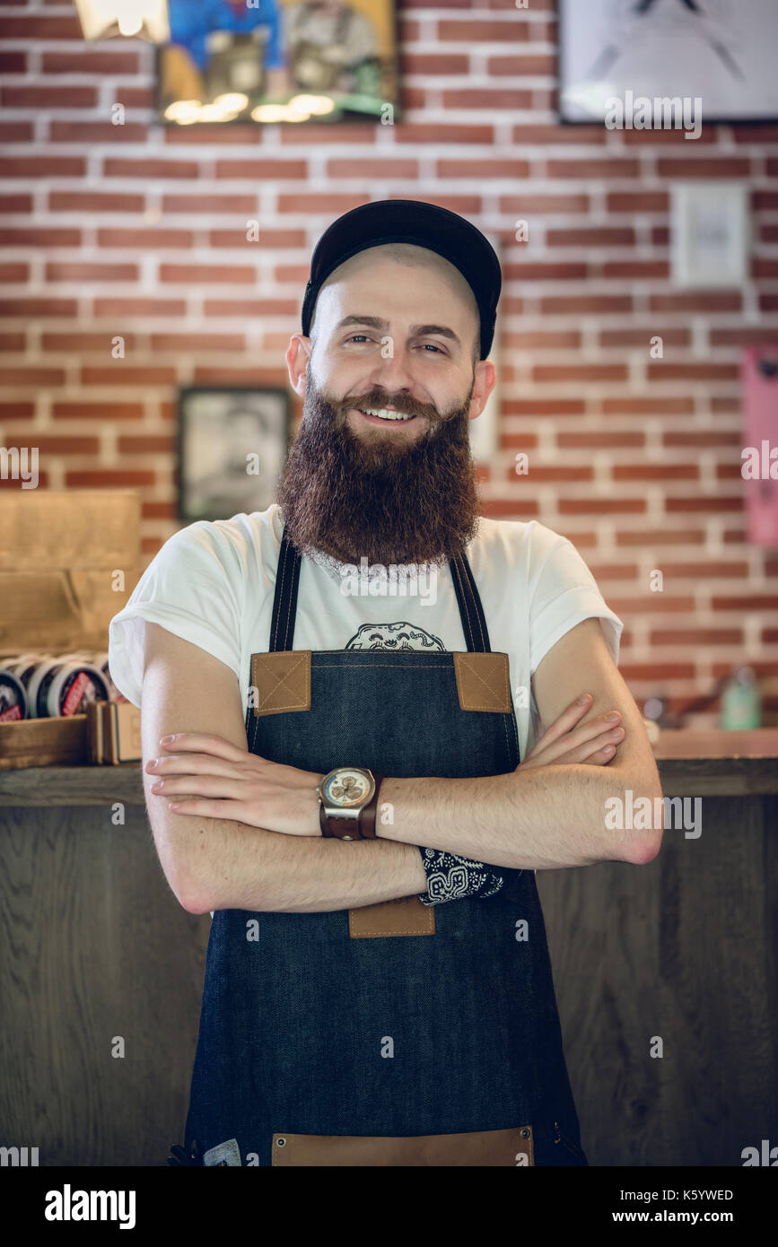 Portrait of a cool hairstylist looking at camera with confidence - Stock Image