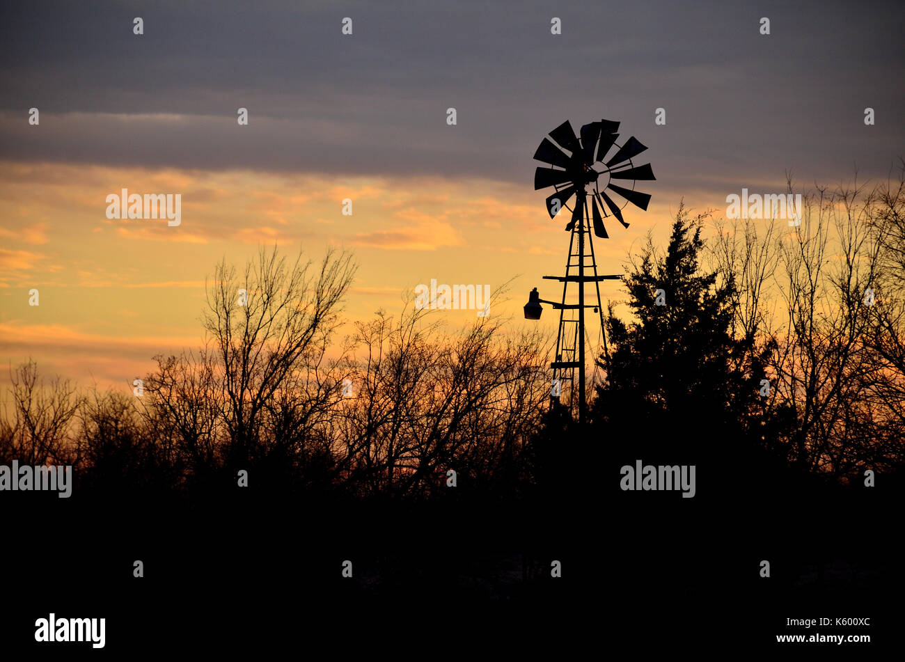 Old farm windmill in silhouette against an Oklahoma sky at sunset. - Stock Image