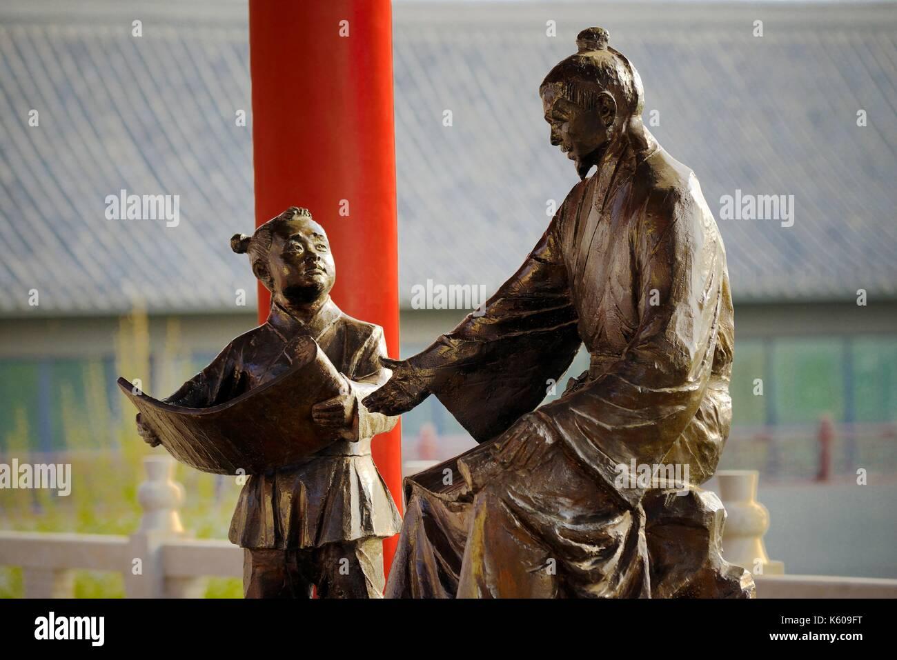 Dongzi Culture Park, Dezhou, China. Statue of Confucian philosopher Dong Zhongshu teaching boy on the rebuilt Reading Platform - Stock Image