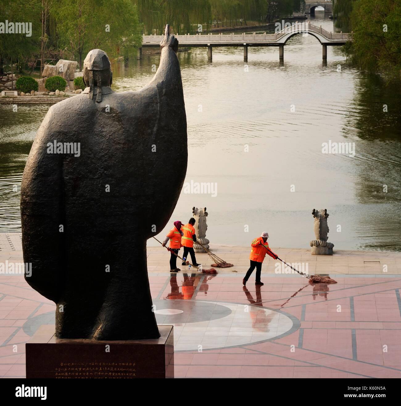 Dongzi Culture Park, City of Dezhou, China. Cleaning the yin yang symbol. Statue of Confucian philosopher Dong Zhongshu - Stock Image