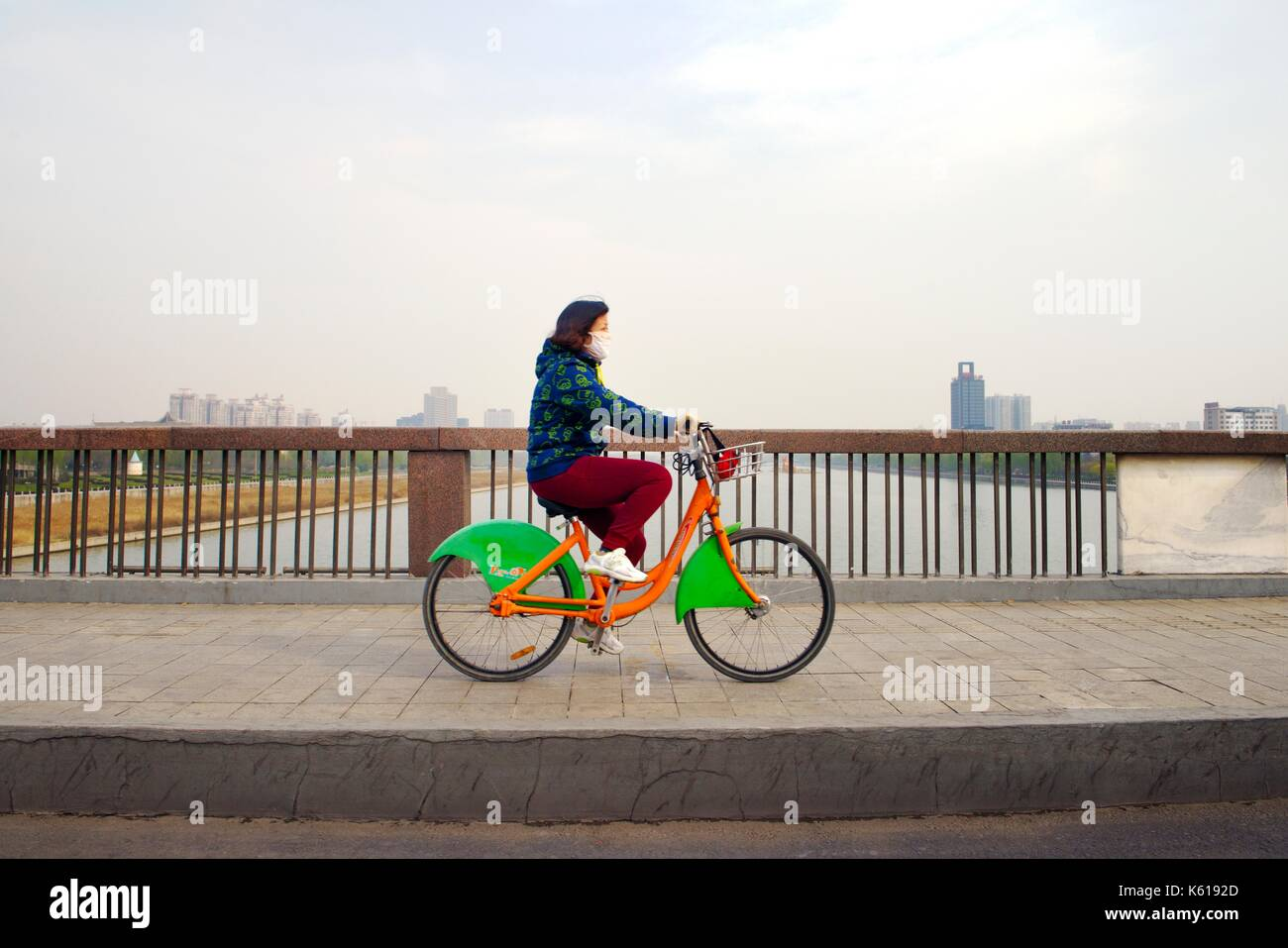 City of Taiyuan, Shanxi, China. Young woman wearing air pollution mask rides city community bike share cycle over the Fen River - Stock Image