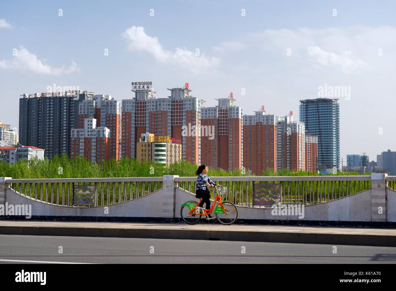 Post-industrial changing City of Taiyuan, Shanxi, China. Cyclist rides bike share in clear clean air past new apartment blocks - Stock Image