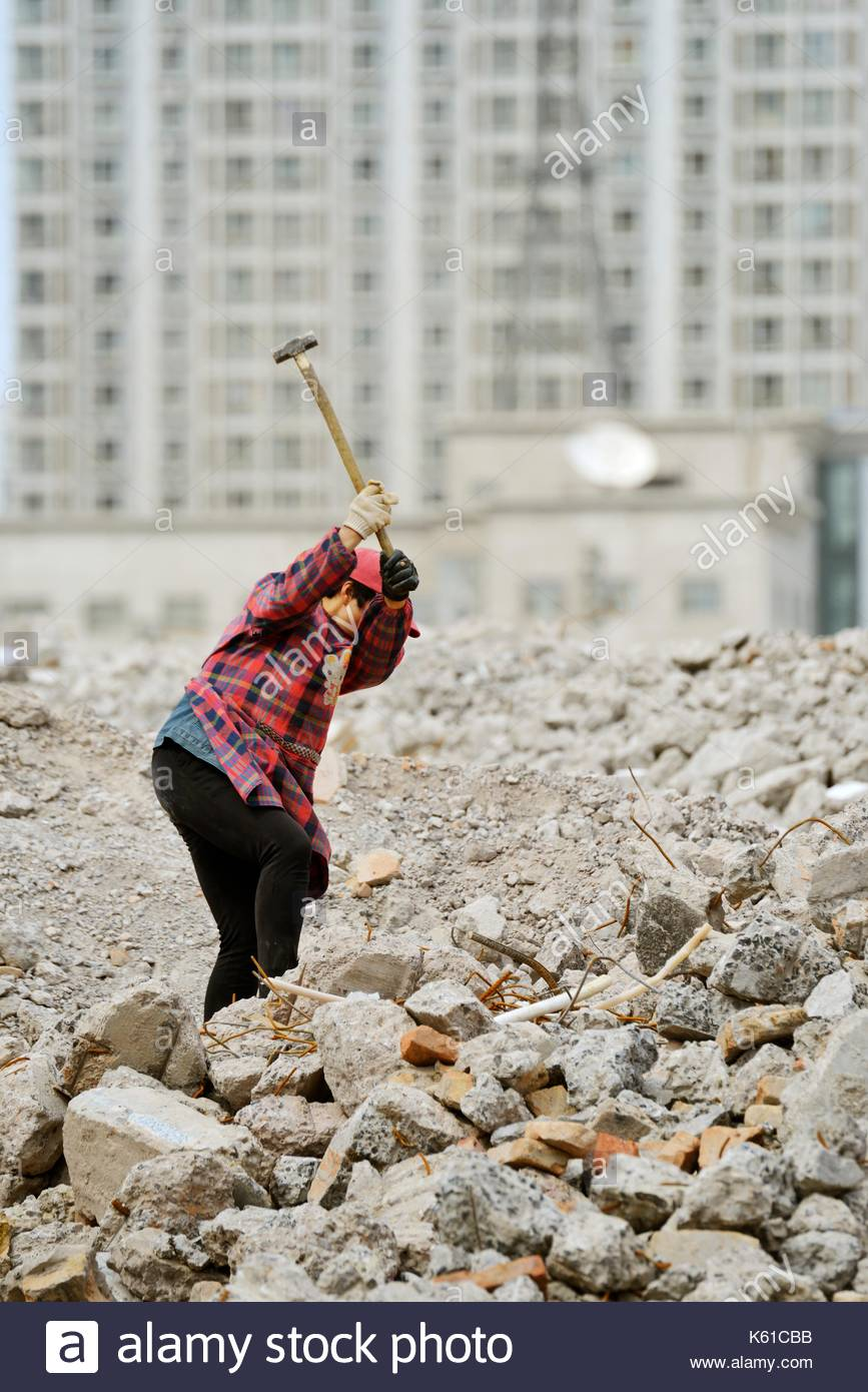 City of Taiyuan, Shanxi Province, China. Worker retrieving metal iron steel rods from hutong demolition debris for recycling - Stock Image