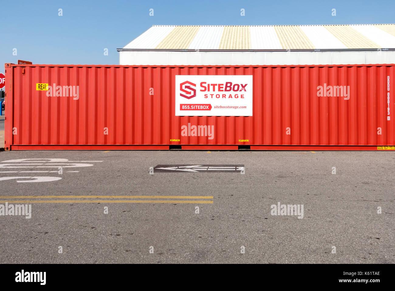 A red metal portable SiteBox storage bin in a Walmart parking lot