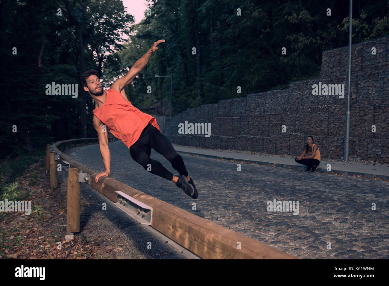 two young people, adventure, road forest outdoors, man jumping fence parkour, street stunt, rural area, woman background behind, jump in air - Stock Image