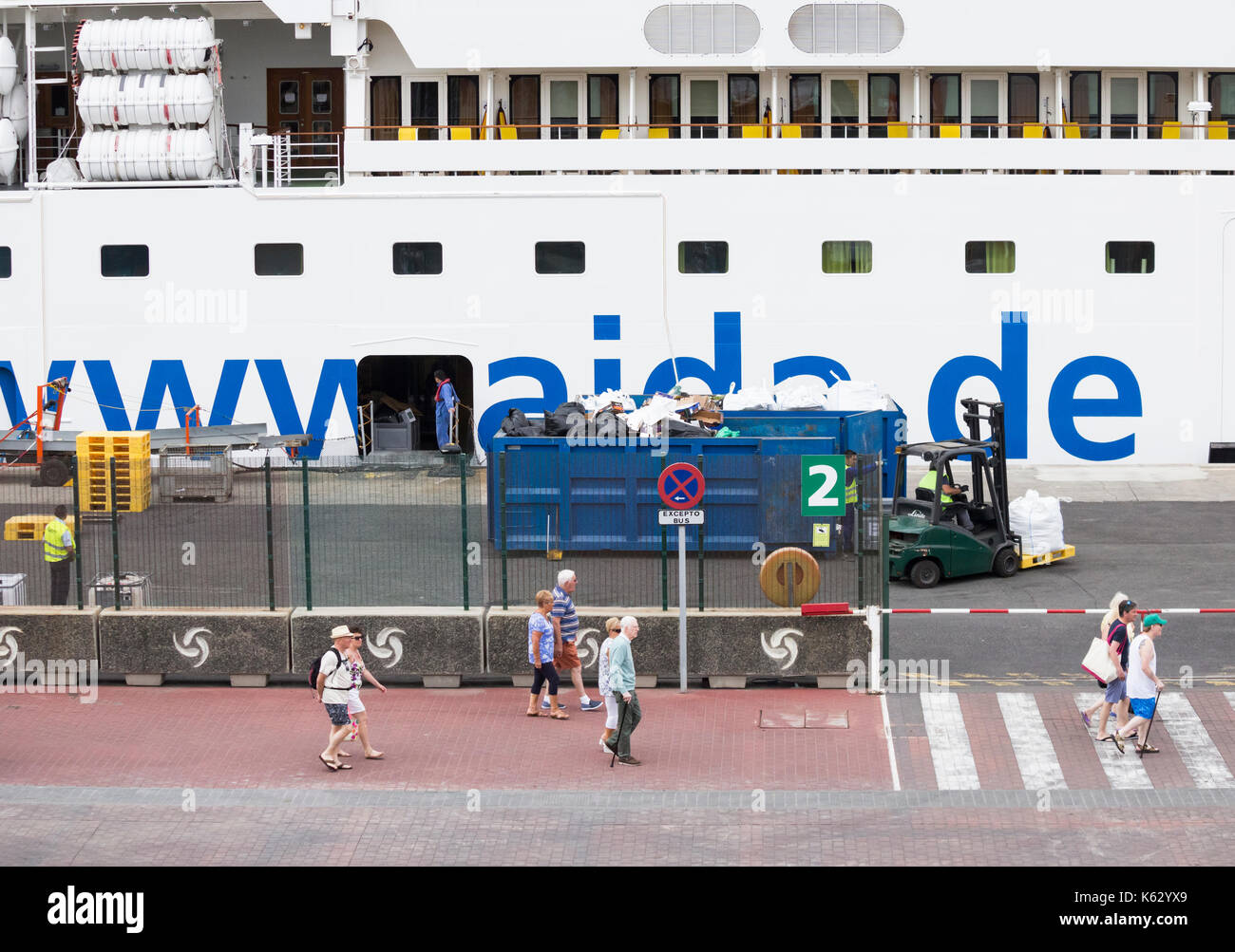 Rubbish from large cruise ship being loaded into containers in port as passengers visit local sites. - Stock Image