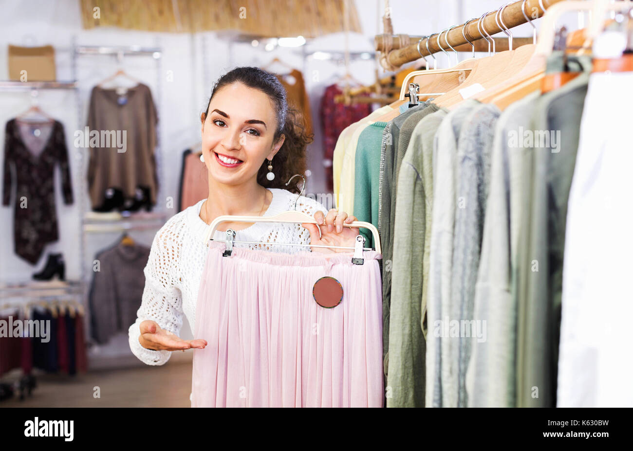 Smiling cheerful woman shopping skirts at the apparel store - Stock Image