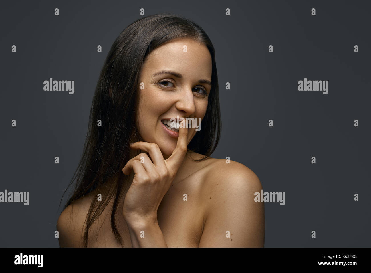 Portrait of young dark-haired seducing woman with bare shoulders against dark background - Stock Image