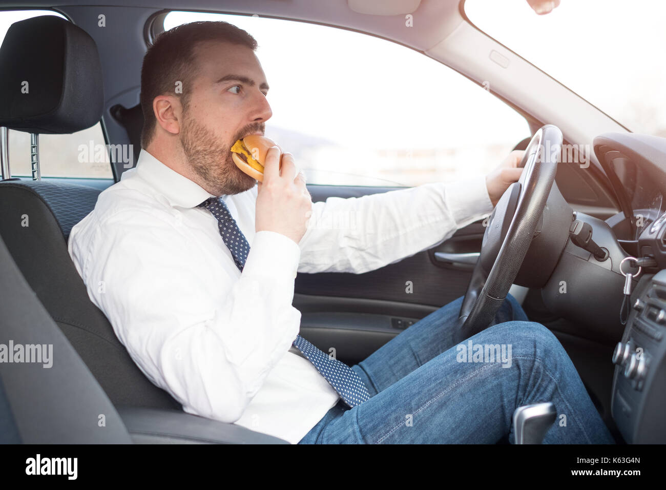 Man eating an hamburger and driving seated in his car - Stock Image