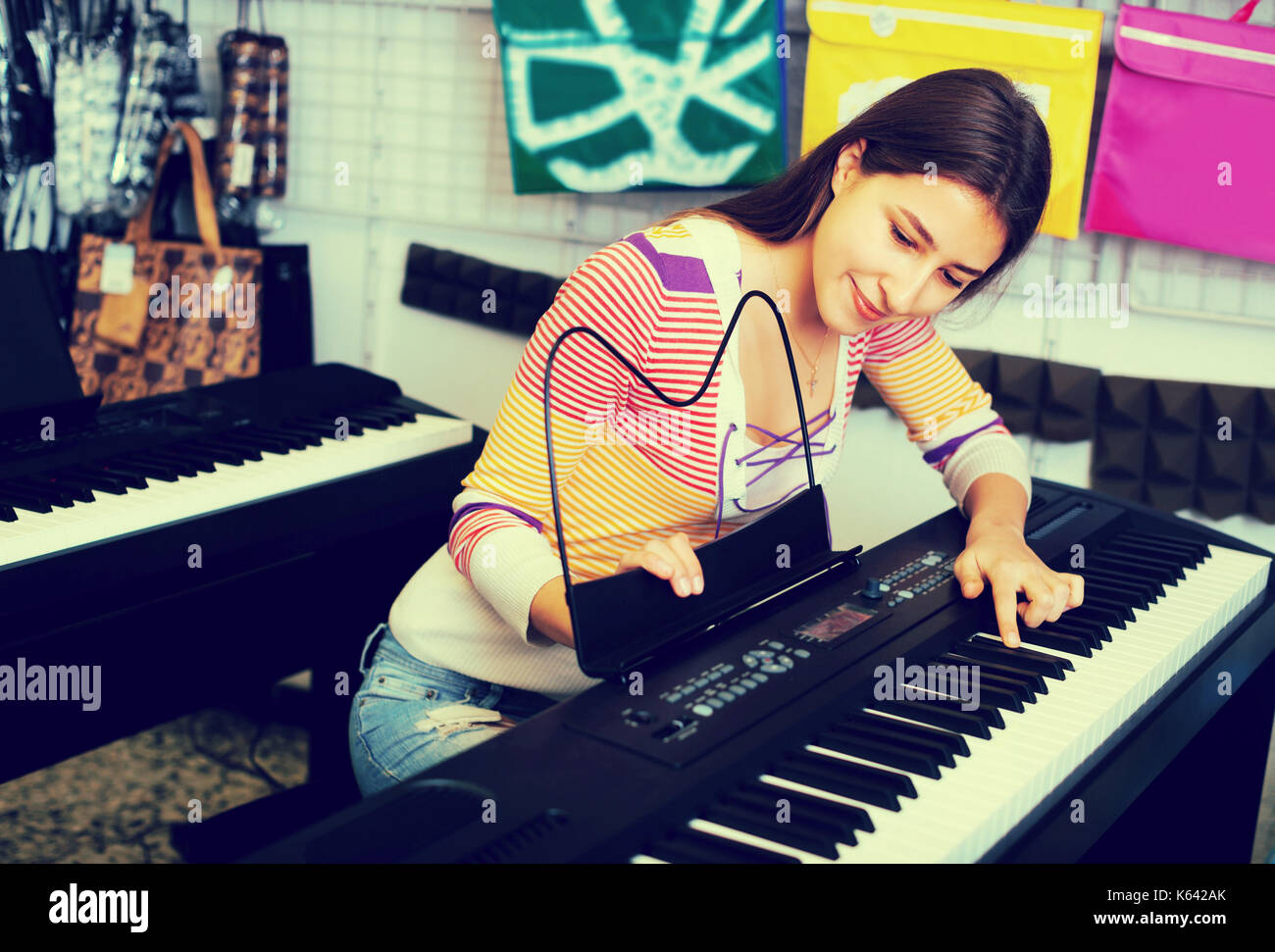 Happy young girl selecting control keyboard for synthesiser in shop - Stock Image