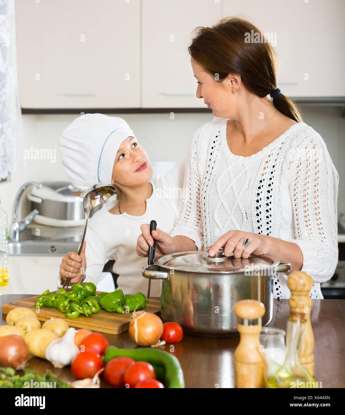 Cheerful daughter and mom cooking with vegetables and casserole at ...