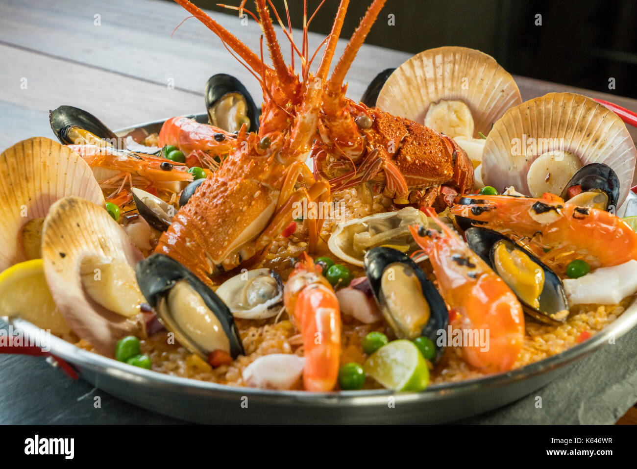 Gourmet seafood Valencia paella with fresh langoustine, clams, mussels and squid on savory saffron rice with prawn, scollops, mussels and lime slices, - Stock Image