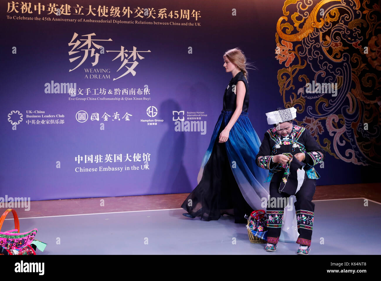 """London, UK. 11th Sep, 2017. A seamstress and a model perform during the """"weaving a dream"""" fashion show celebrating Stock Photo"""