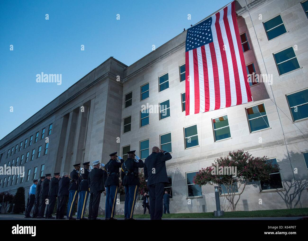 Arlington, United States Of America. 11th Sep, 2017. First Responders salute a large American flag as it is unfurled over the west side of the Pentagon at sunrise in preparation for an the ceremony commemorating the anniversary of the 9/11 terrorist attacks at the Pentagon September 11, 2017 in Arlington, Virginia. The aircraft impacted the building where the flag is unfurled. Credit: Planetpix/Alamy Live News - Stock Image