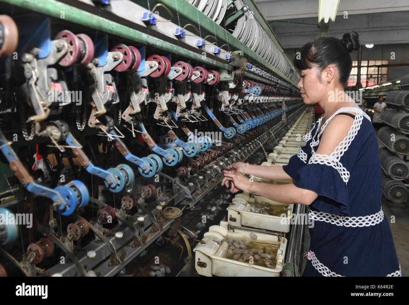 Nanchong, China's Sichuan Province. 11th Sep, 2017. A worker is seen on a textile production line at Liuhe Group in Nanchong, southwest China's Sichuan Province, Sept. 11, 2017. Nanchong enjoyed fame of a 'city of silk' which has a complete industry that covers mulberry-growing, silkworm-raising, silk production, silk fabric processing and education and research on sericulture and silk production. Credit: Liu Kun/Xinhua/Alamy Live News - Stock Image