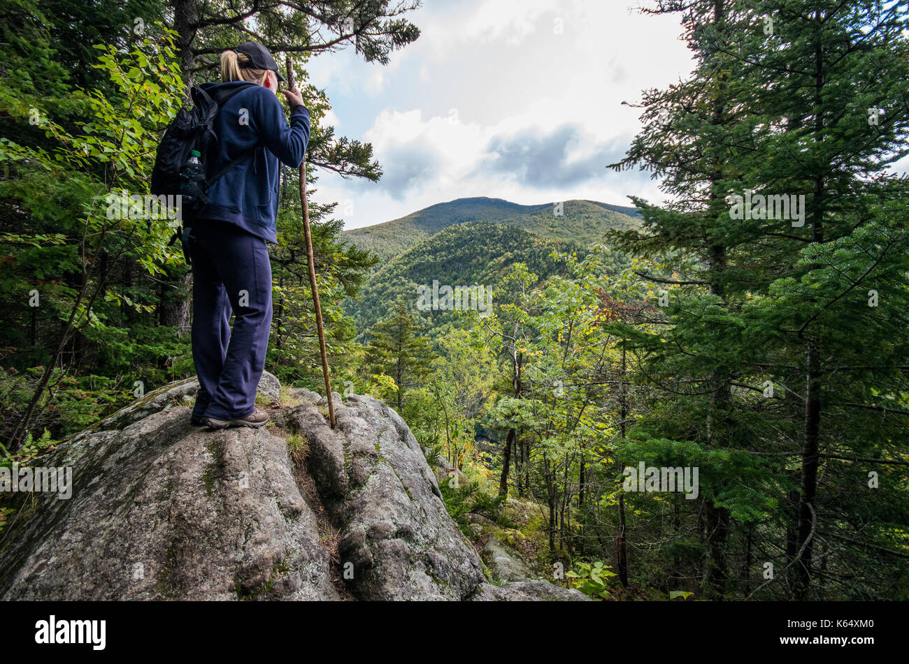 Woman looking over a cliff on Pitchoff Mountain in Keene New York - Stock Image